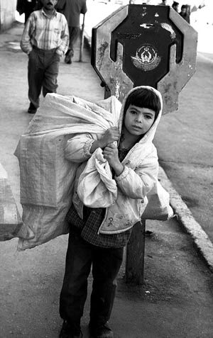 ein obdachloses Mädchen, hinter ihm der öffentliche Spendenkasten mit Allahs Zeichen drauf