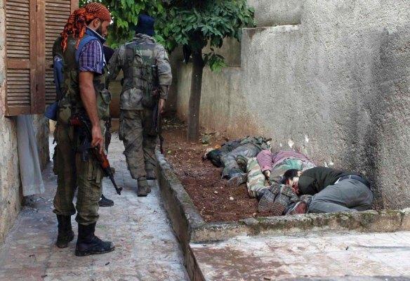 REUTERS- Rebellenkämpfer durchsuchen ein Haus in der Stadt Harem im Norden des Landes nach Anhängern von Baschar al-Assad. Einer bleibt stehen und blickt auf die zusammengekauerten Leichen an der Mauer. Die getöteten Männer sollen Assad-Unterstützer gewesen sein. sie von den Rebellen hingerichtet.