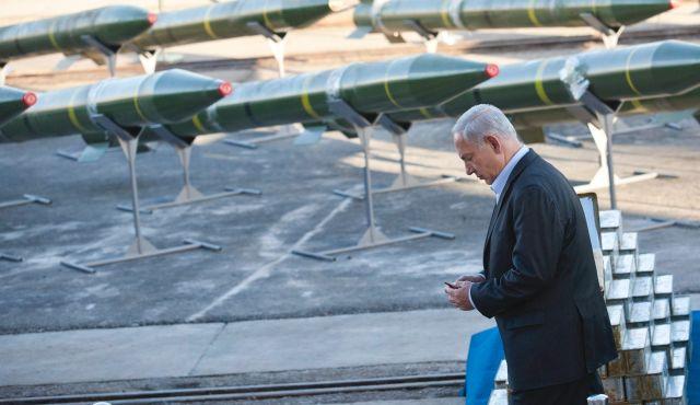 Ministerpräsident Benjamin Netanjahu, hält eine Kugel in den Händen, während er neben beschlagnahmten Raketen an Deck der Klos C steht.